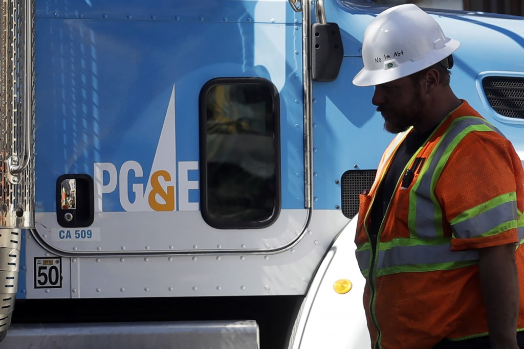 FILE - In this Aug. 15, 2019, file photo, a Pacific Gas & Electric worker walks in front of a truck in San Francisco. Pacific Gas & Electric and a gro