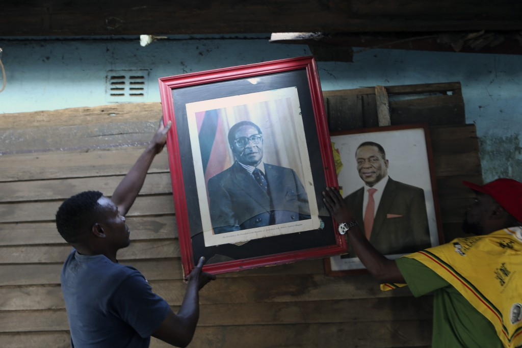 Supporters of Former Zimbabwean President Robert Mugabe place his portrait next to that of Zimbabwean President Emmerson Mnangagwa in Harare, Tuesday,...