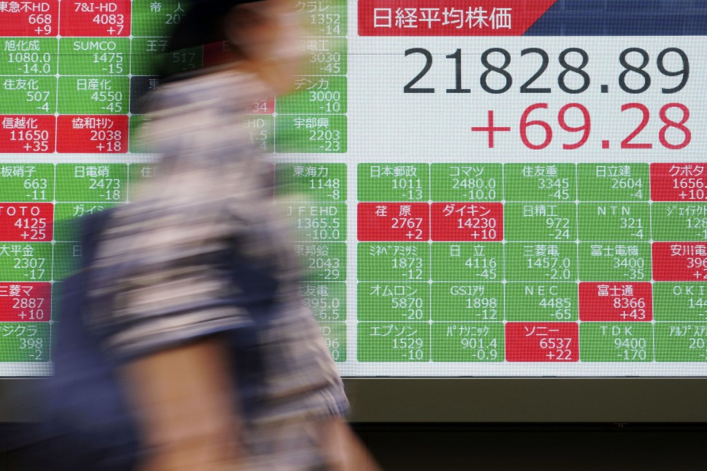 A person walks past an electronic stock board showing Japan's Nikkei 225 index at a securities firm in Tokyo Friday, Sept. 13, 2019. Stocks were broad...
