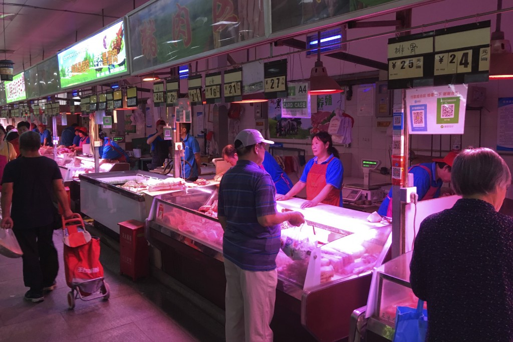 In this Wednesday, Sept. 11, 2019, photo, customers shop for pork at a meat market in Beijing. Chinese families are having to rethink menu options as