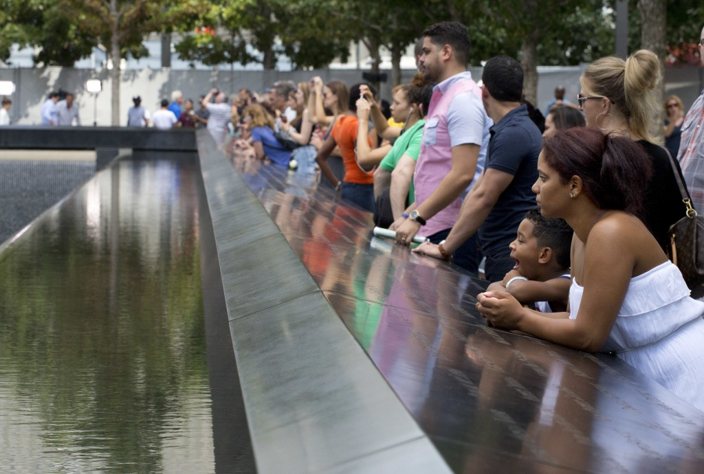 FILE- In this Sept. 9, 2015 file photo, visitors look at the waterfalls at the World Trade Center Memorial in New York. As they have done 17 times bef