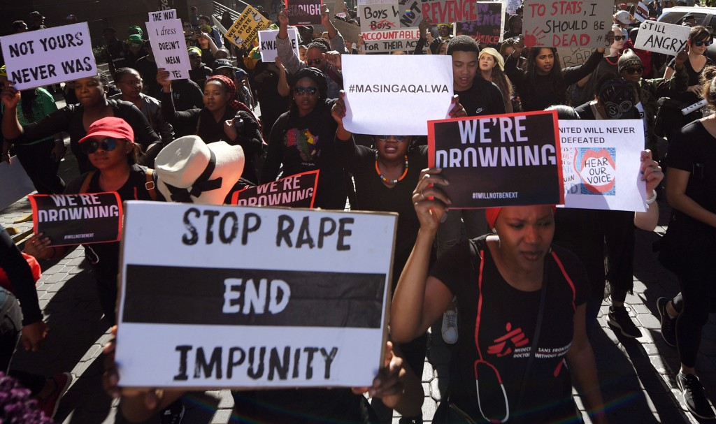 Demonstrators hold up banners in Sandton, Johannesburg, Friday Sept. 13, 2019, as they protest against gender-based violence. The protesters are calli