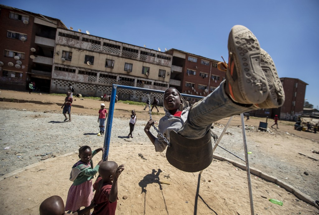 Children play on swings in the low income neighborhood of Mbare, known to have many supporters of former president Robert Mugabe's ZANU-PF party, in t