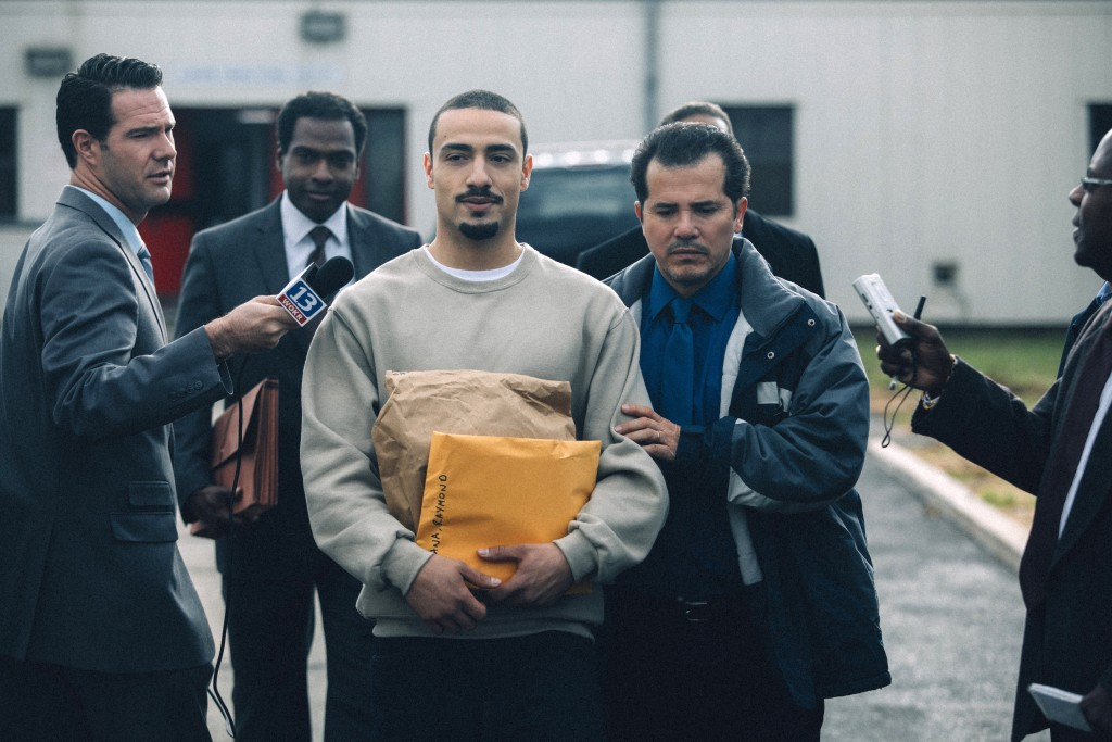 """This image released by Netflix shows Freddy Miyares as Adult Raymond Santana Jr. and John Leguizamo as Raymond Santana Sr., right, in a scene from """"Wh..."""