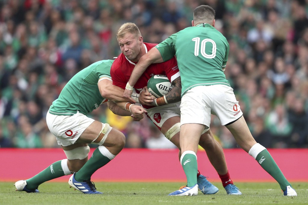 Wales' Ross Moriarty is tackled by Ireland's Johnny Sexton, right, during the summer series rugby match between Wales and Ireland at the Aviva Stadium...