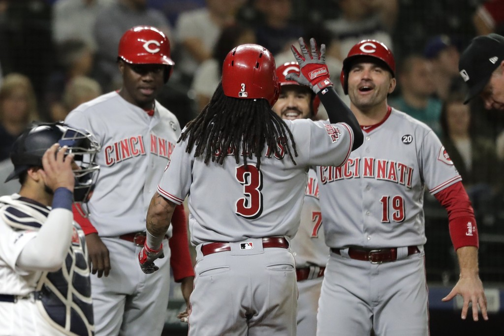 Cincinnati Reds' Freddy Galvis (3) is greeted by, from left, Aristides Aquino, Eugenio Suarez and Joey Votto, after the three scored on Galvis' grand