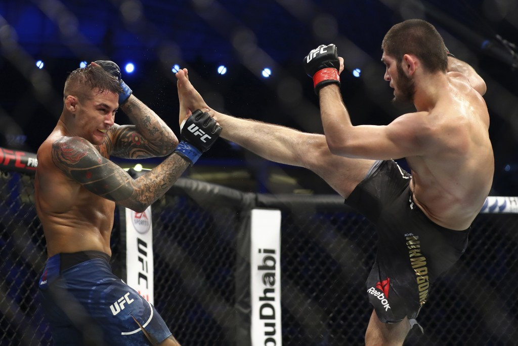 Russian UFC fighter Khabib Nurmagomedov, right, kicks UFC fighter Dustin Poirier, of Lafayette, La., during Lightweight title mixed martial arts bout