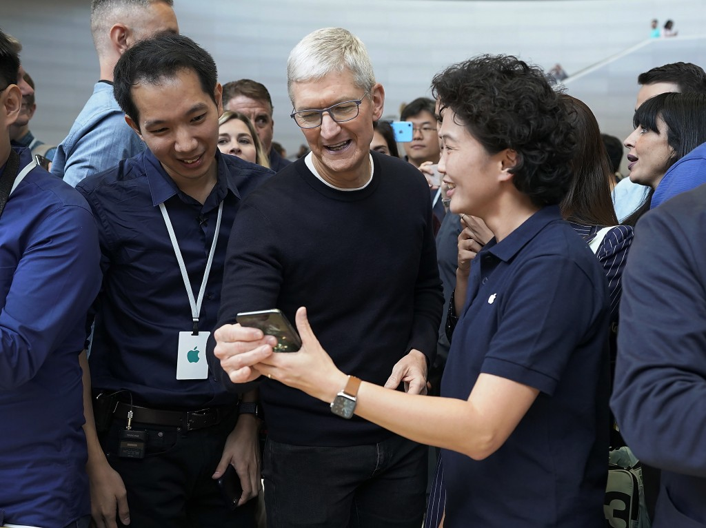 Apple CEO Tim Cook, center, looks at the the new iPhone 11 Pro Max, during an event to announce new products Tuesday, Sept. 10, 2019, in Cupertino, Ca...