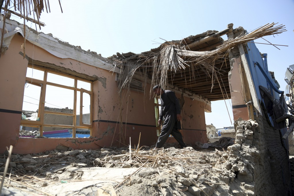 In this Tuesday, Sept. 10, 2019, photo, Samiullah inspects the remains of his damaged house after a large explosion last week near a compound housing ...