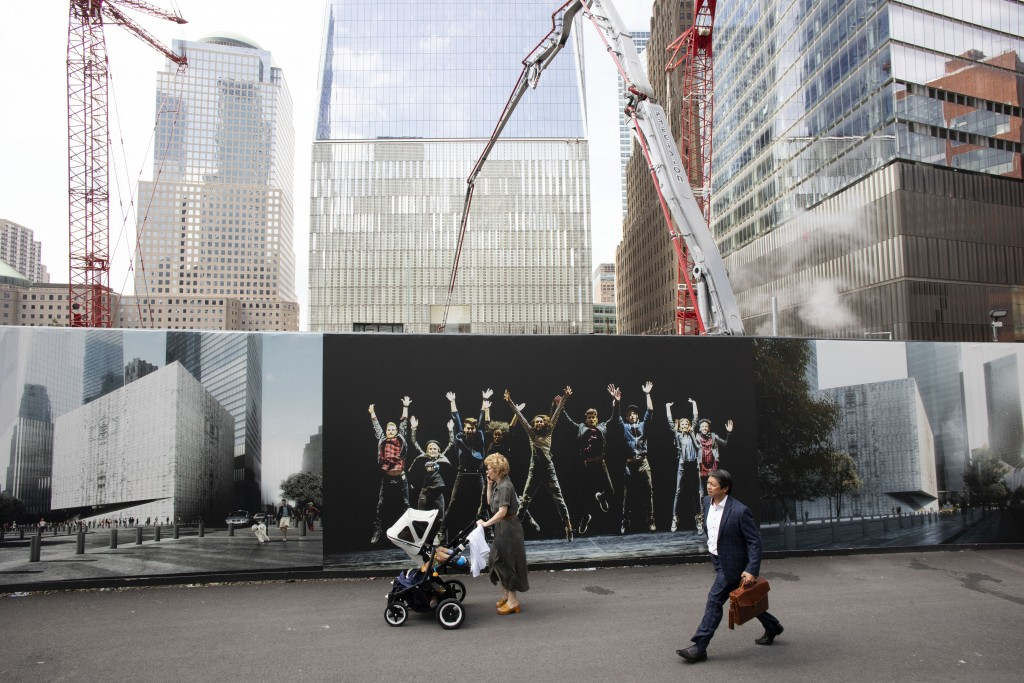 People walk by murals promoting the future site of the Ronald O. Perelman Performing Arts Center as cranes work over the site at the World Trade Cente