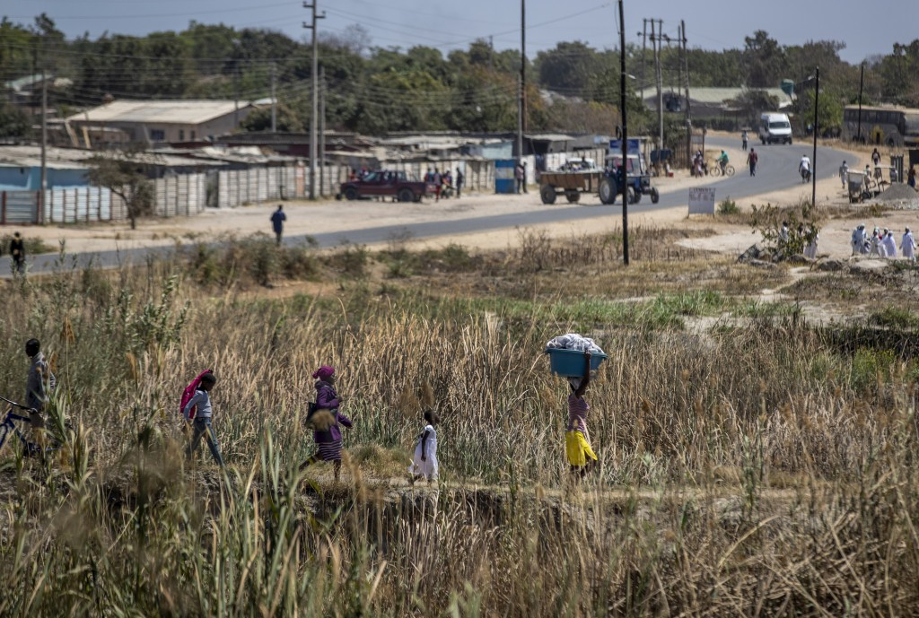 Zimbabwean women and girls walk down a path as they return from church and from washing their clothes in a nearby lake, on the outskirts of Harare, Zi