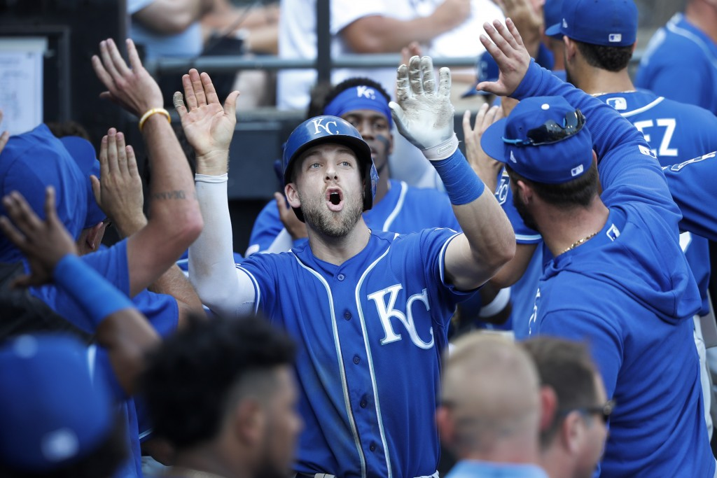 Kansas City Royals' Hunter Dozier celebrates in the dugout his three-run home run off Chicago White Sox starting pitcher Lucas Giolito during the sixt...