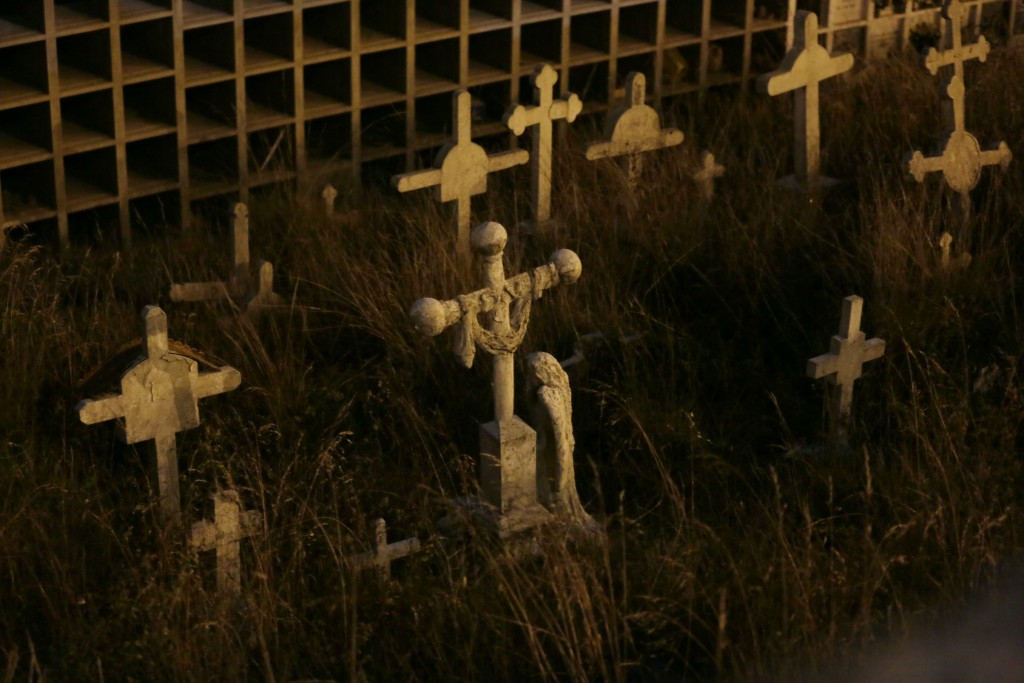 Crosses stand on El Tejar cemetery's potters field in Quito, Ecuador, Wednesday, Sept. 11, 2019. Many tourists said they found the night visit to the
