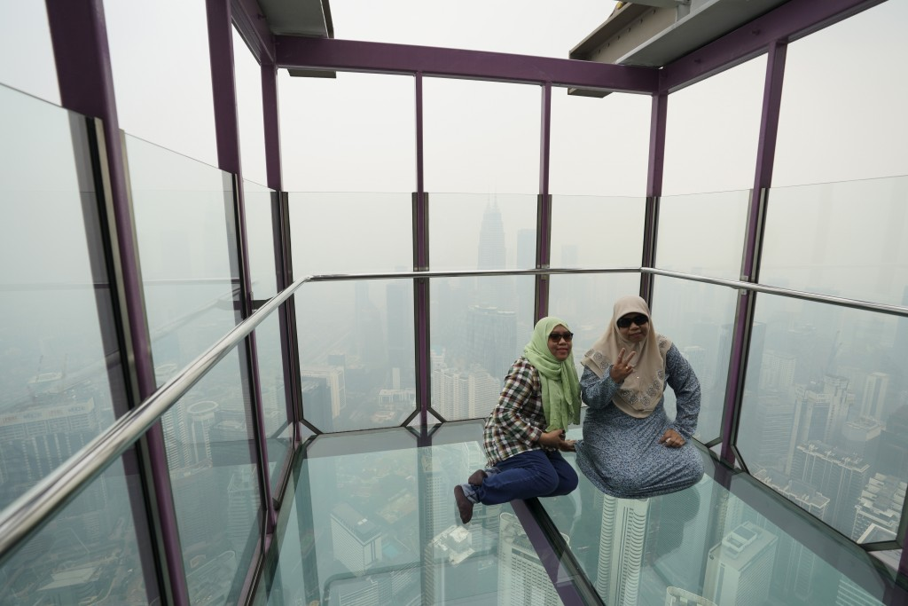 Tourists pose for a photo at Skybox at Kuala Lumpur Tower as city stands shrouded with haze in Kuala Lumpur, Malaysia, Friday, Sept. 13, 2019. Malaysi...
