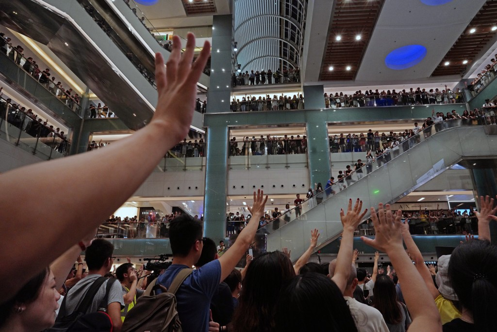 "Protesters gesture as they sing a theme song written by protesters ""Glory be to thee"" at a shopping mall in Hong Kong Wednesday, Sept. 11, 2019. Hundr"
