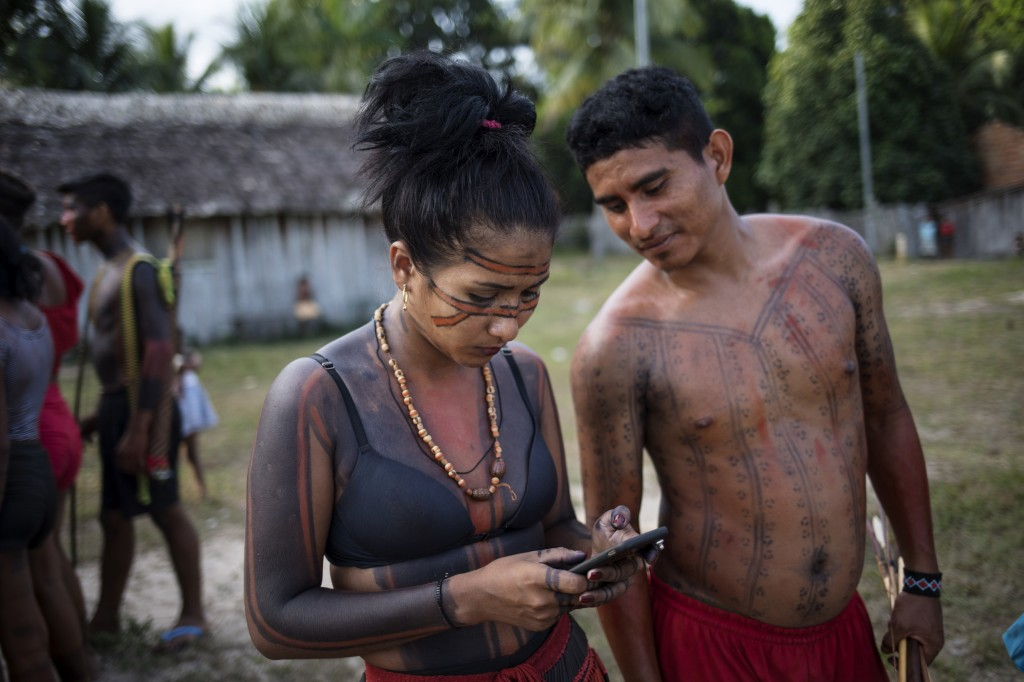 In this Sept. 3, 2019 photo, a woman checks her cell phone during a meeting of Tembé tribes at the Tekohaw indigenous reserve, Para state, Brazil. Som...