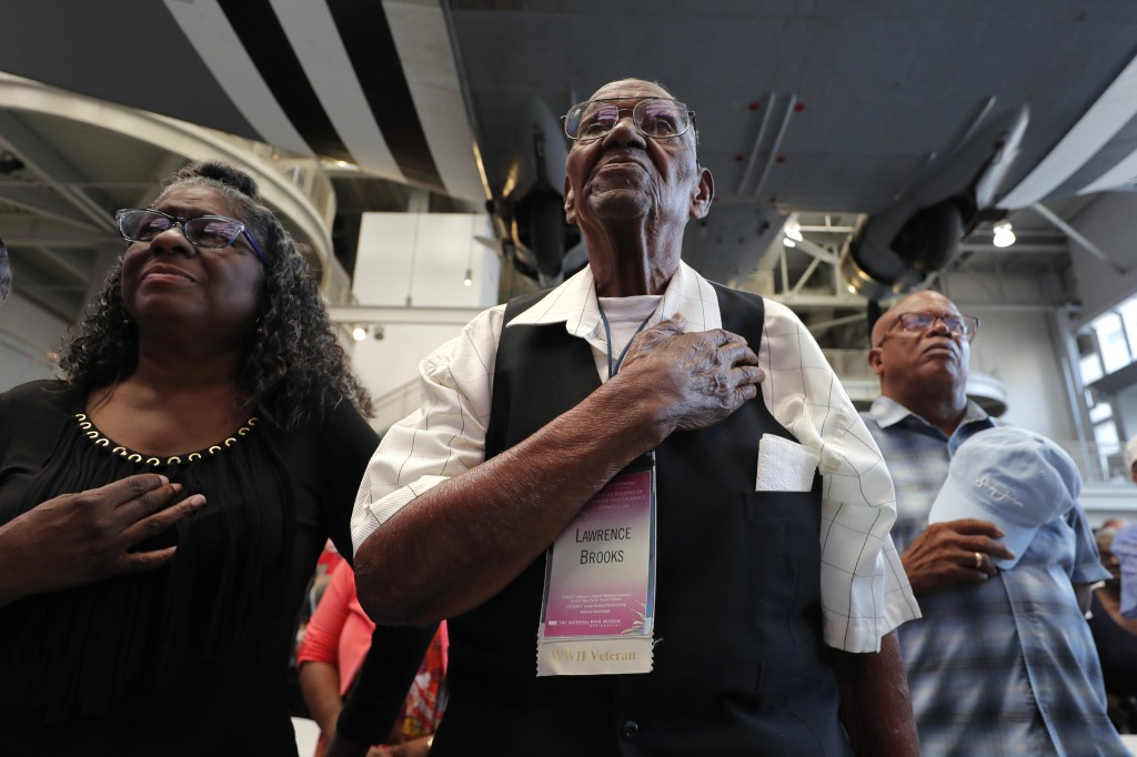 World War II veteran Lawrence Brooks holds his hand to his heart during the singing of the National Anthem as he celebrates his 110th birthday at the