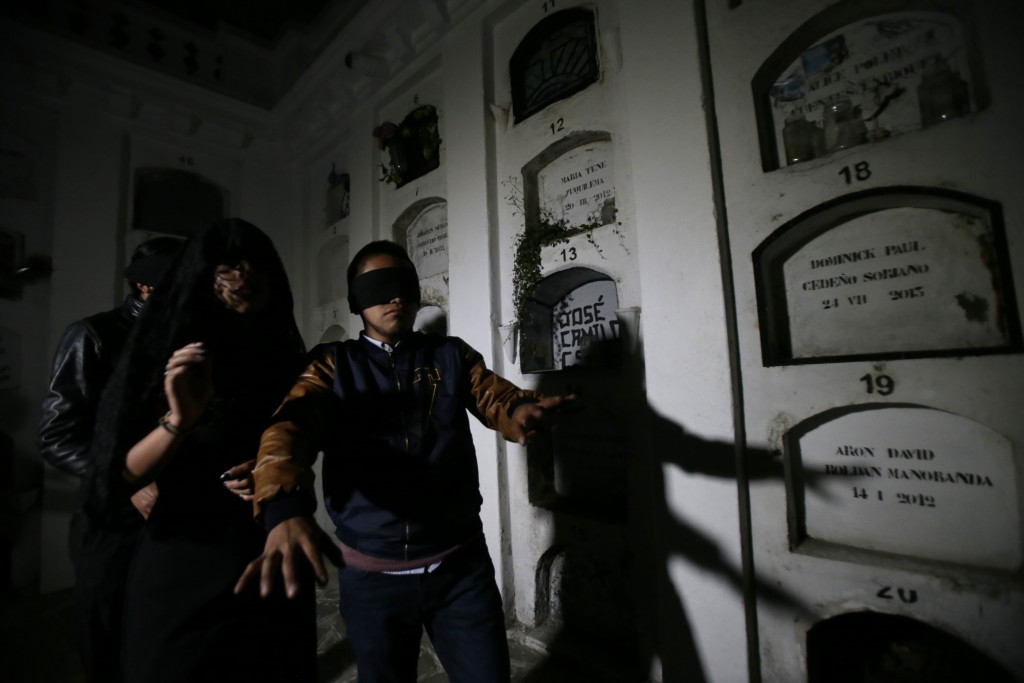 Blindfolded tourists walk through El Tejar cemetery, in downtown Quito, Ecuador, Wednesday, Sept. 11, 2019. They're there to get a taste of death whil