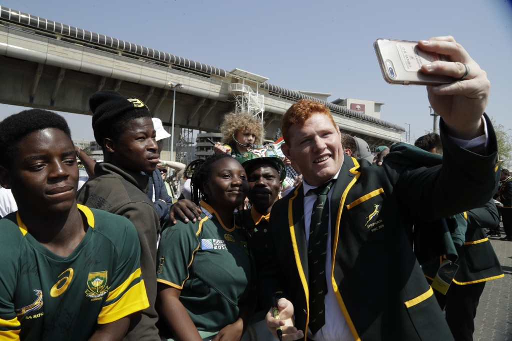 South Africa's rugby coach Rassie Erasmus, takes a selfie photo with fans at a farewell ceremony at the O.R. Thabo Airport in Johannesburg Friday Aug....