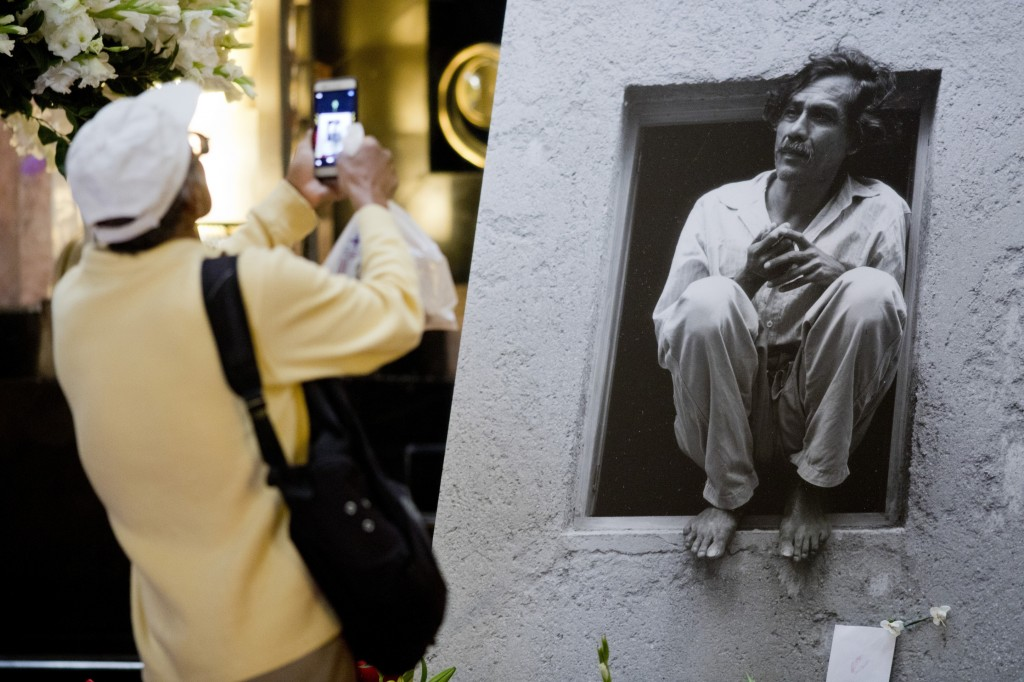 In this Sept. 6, 2019 photo, a man takes a photo of a photograph of the late Mexican painter Francisco Toledo during a memorial at the Bellas Artes Pa...
