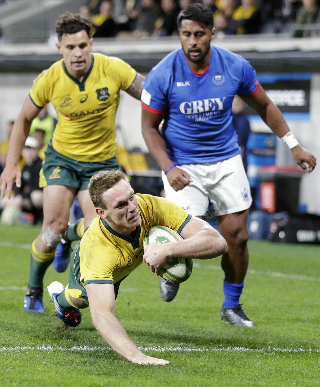 Australia's Dane Haylett-Petty, bottom, dives over to score a try against Samoa during their rugby union test match in Sydney, Saturday, Sept. 7, 2019...