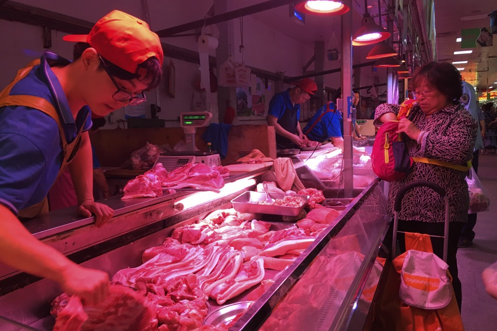 In this Wednesday, Sept. 11, 2019, photo, a clerk stacks cuts of pork at a meat market in Beijing. Chinese families are having to rethink menu options