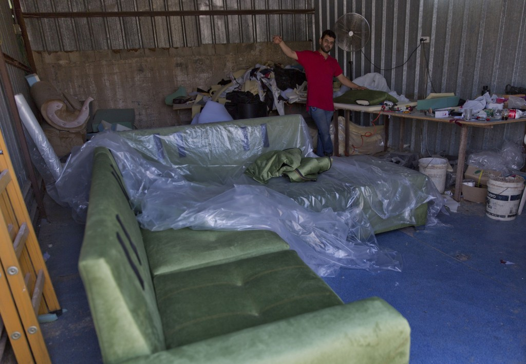 In this Wednesday, Sept. 11, 2019 photo, a Palestinian carpenter works on living room furniture that was ordered by an Israeli settler, at his worksho