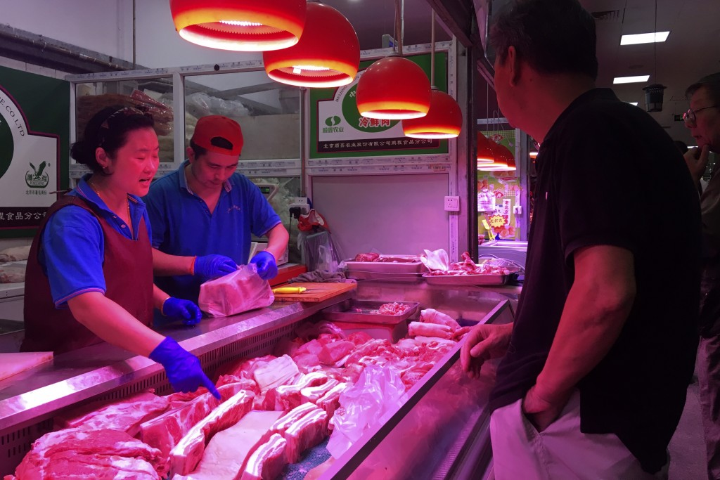 In this Wednesday, Sept. 11, 2019, photo, clerks help a customer shop for pork at a meat market in Beijing. Chinese families are having to rethink men