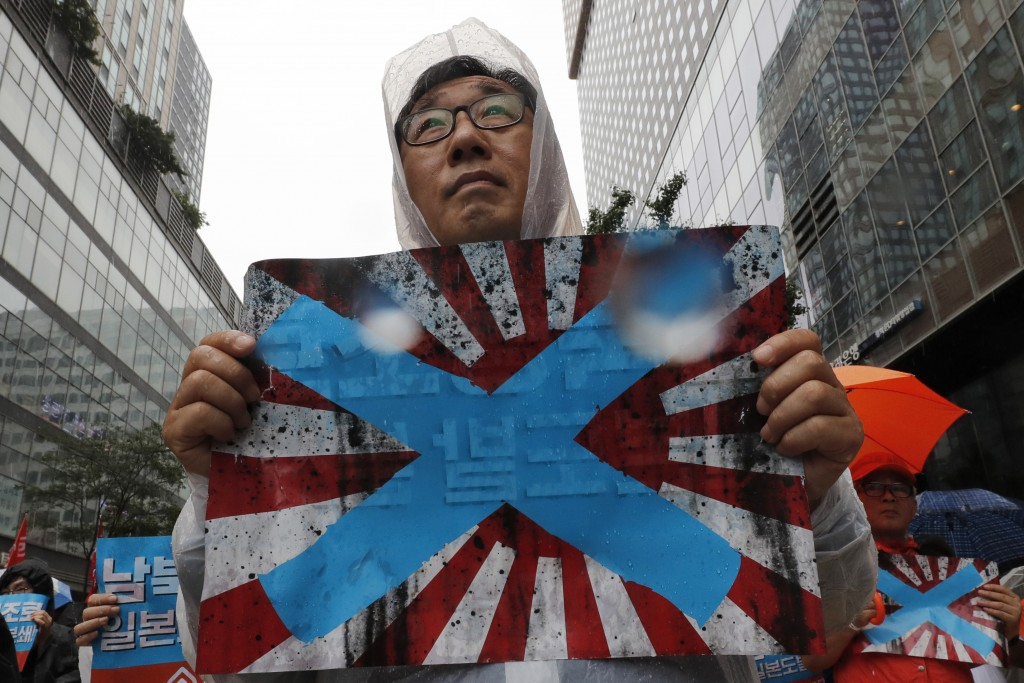 FIEL - In this Aug. 15, 2019, file photo, South Korean protesters hold Japanese rising sun flags during a rally to mark the South Korean Liberation Da...