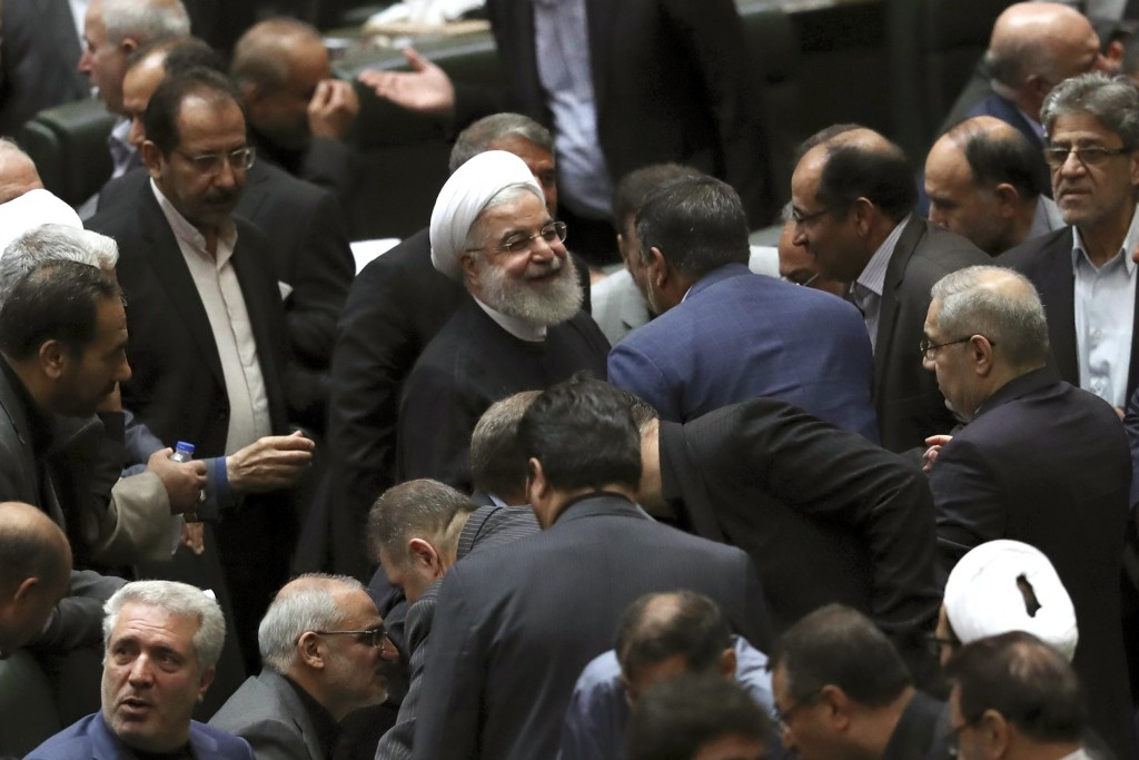 Iranian President Hassan Rouhani, center, listens to a lawmaker after defending his proposed tourism and education ministers, in Tehran, Iran, Tuesday