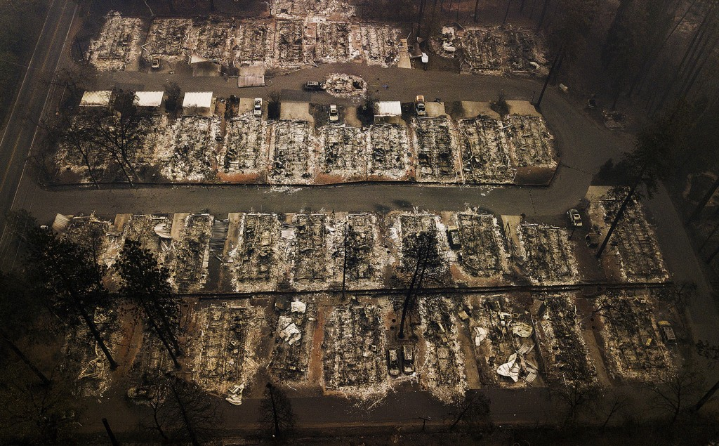 FILE - This Nov. 15, 2018, aerial file photo shows the remains of residences leveled by the Camp wildfire in Paradise, Calif. Pacific Gas & Electric a...
