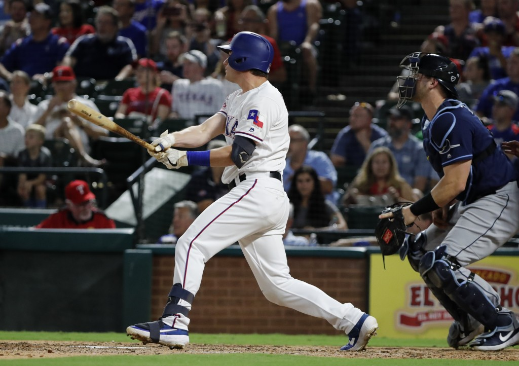 Texas Rangers' Nick Solak watches his two-run home run, next to Tampa Bay Rays catcher Mike Zunino during the fourth inning of a baseball game in Arli...
