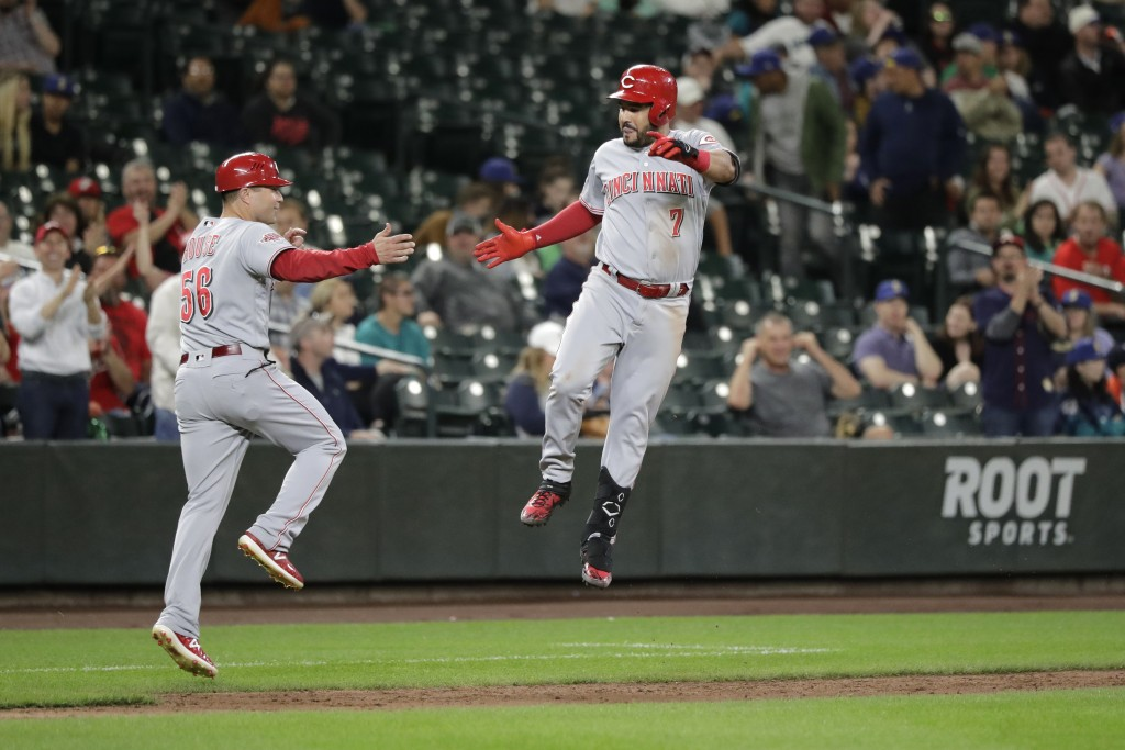 Cincinnati Reds' Eugenio Suarez, right, leaps as he is greeted by third base coach J.R. House after Suarez hit a two-run home run during the eighth in