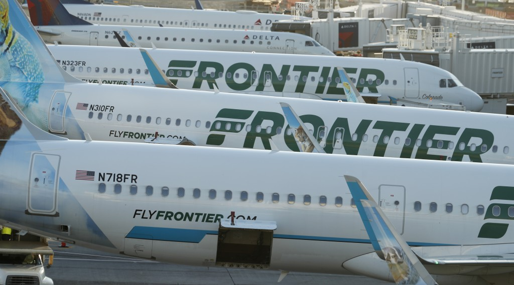 In this June 26, 2019 photo Frontier Airlines jetliners sit at gates on the A concourse at Denver International Airport in Denver. A new report says U...