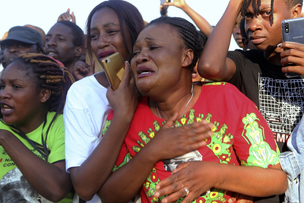 Supporters of Zimbabwe's former ruler, Robert Mugabe react upon the arrival of his remains at at RG Mugabe airport in Harare,Wednesday, Sept, 11, 2019...
