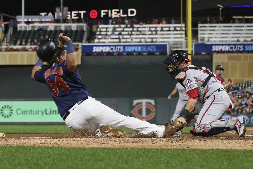 Washington Nationals catcher Yan Gomes, right, tags out Minnesota Twins' Willians Astudillo on a fielder's choice at the plate in the second inning of...