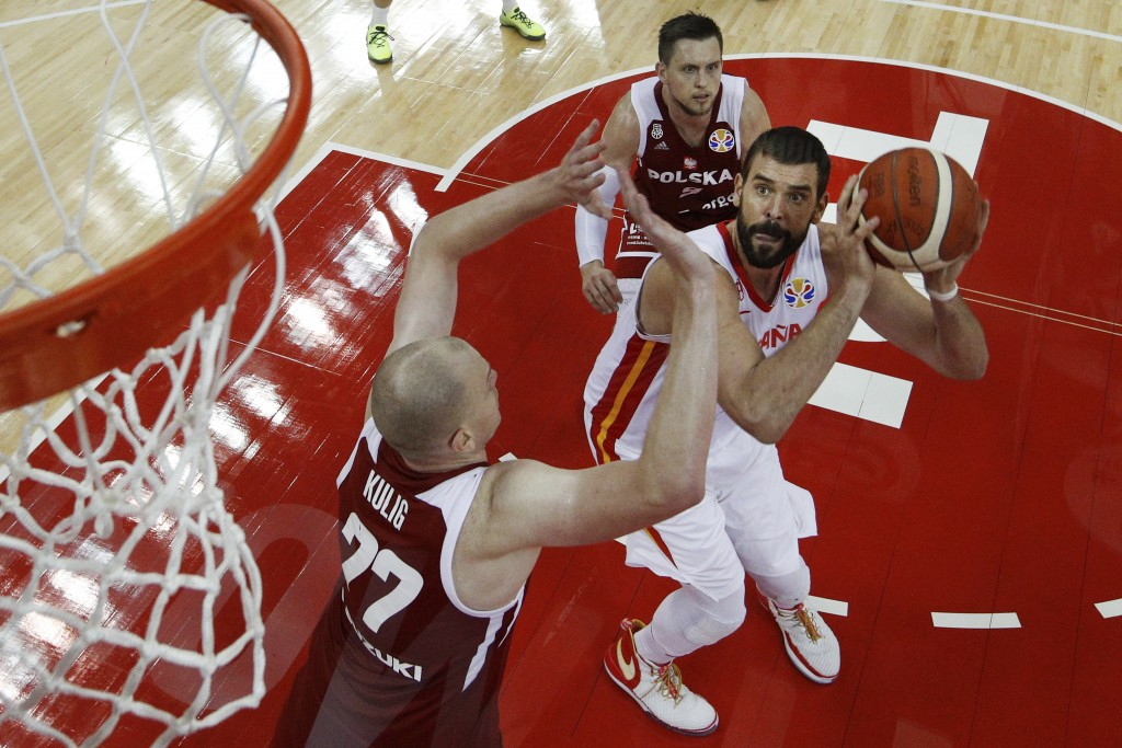Marc Gasol of Spain prepares to put up a shot over Damian Kulig, left, during their quarterfinals match for the FIBA Basketball World Cup, at the Shan