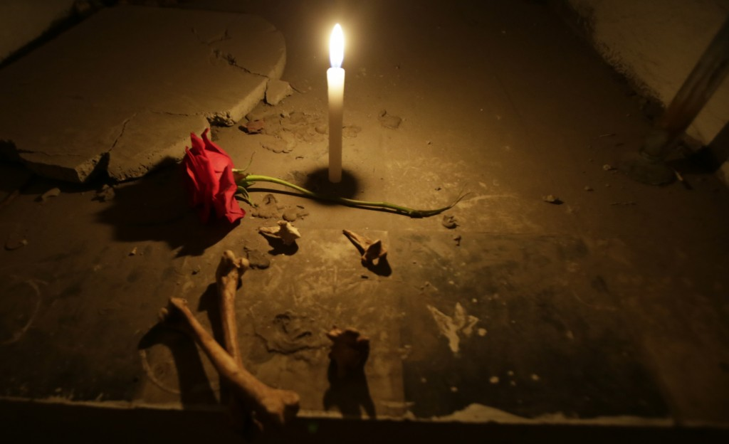A candle burns inside an empty mausoleum at El Tejar cemetery, in downtown Quito, Ecuador, Wednesday, Sept. 11, 2019. On a recent evening, 13 visitors