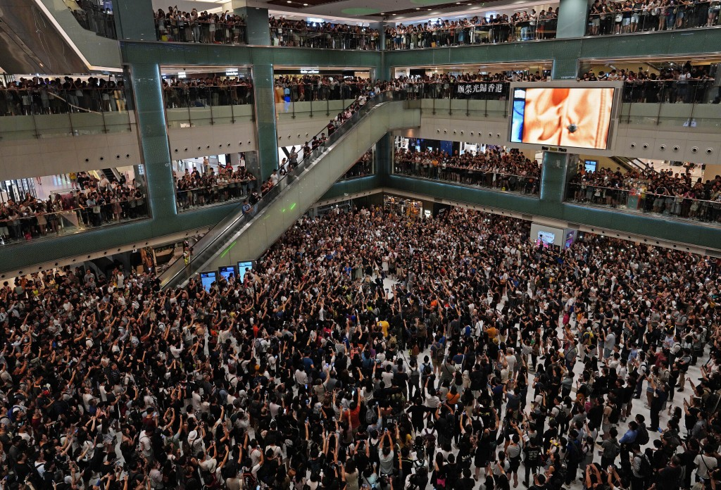 "In this Wednesday, Sept. 11, 2019, file photo, local residents sing a theme song written by protesters ""Glory be to thee"" at a shopping mall in Hong K"