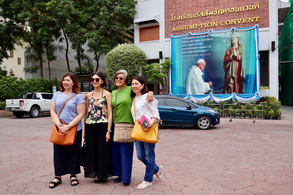 In this Sept. 8, 2019, photo, Catholic churchgoers pose in front of Pope Francis image outside a church in Bangkok, Thailand. The Vatican said Friday,
