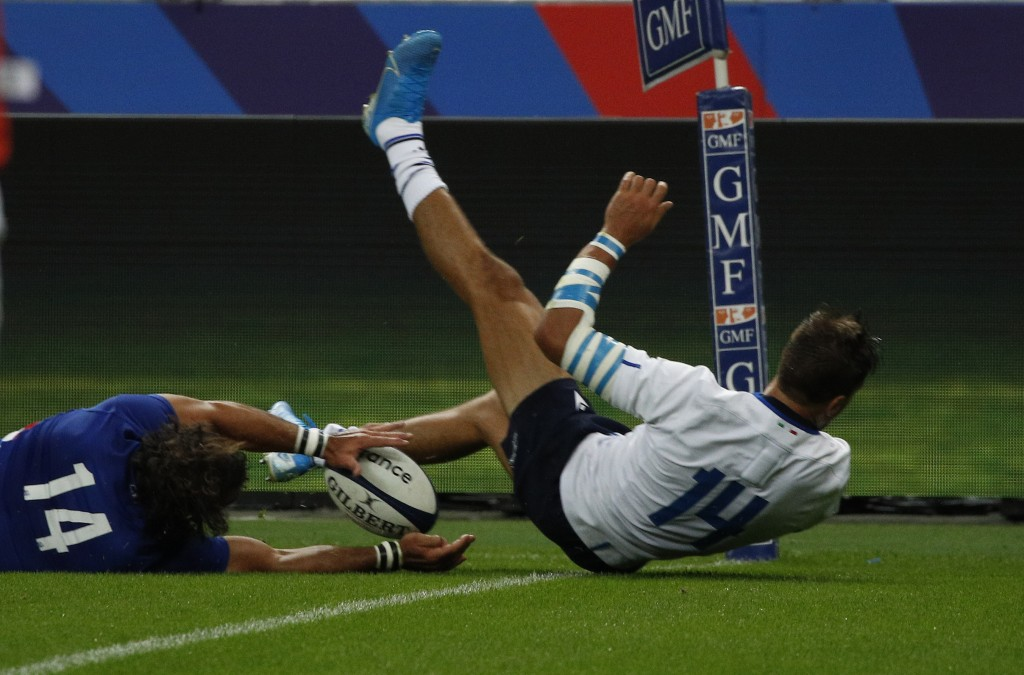 France's Damian Penaud, left, scores his team second try as Italy's Mattia Bellini tries to defend during a friendly rugby test match between France a