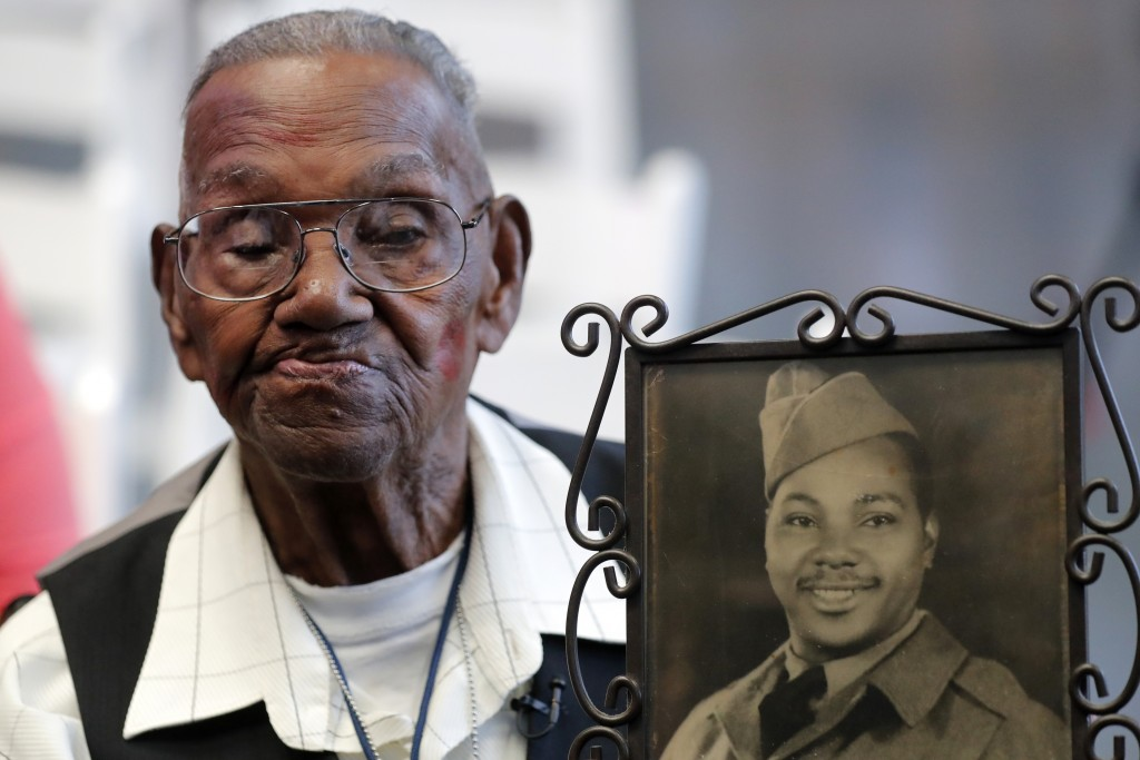 World War II veteran Lawrence Brooks holds a photo of him taken in 1943, as he celebrates his 110th birthday at the National World War II Museum in Ne