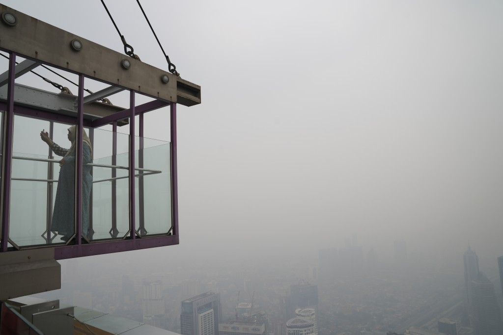 Tourists take a selfie from Kuala Lumpur Tower as city stands shrouded with haze in Kuala Lumpur, Malaysia, Friday, Sept. 13, 2019. Malaysian authorit...