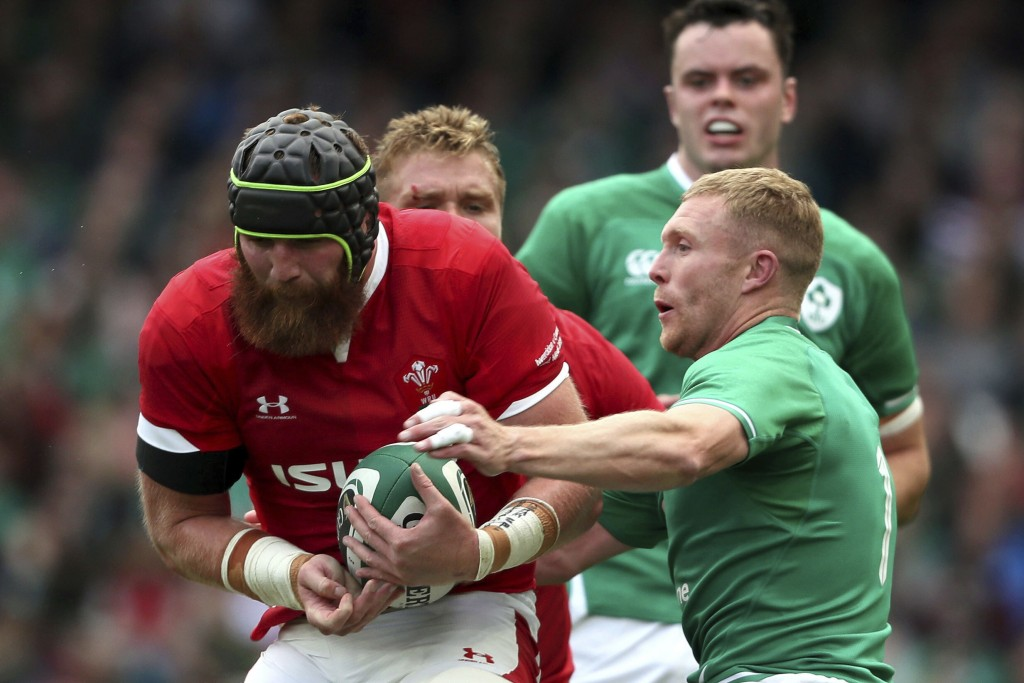 Wales' Jake Ball, left, is tackled by Ireland's Keith Earls during the summer series rugby match between Wales and Ireland at the Aviva Stadium, Dubli...