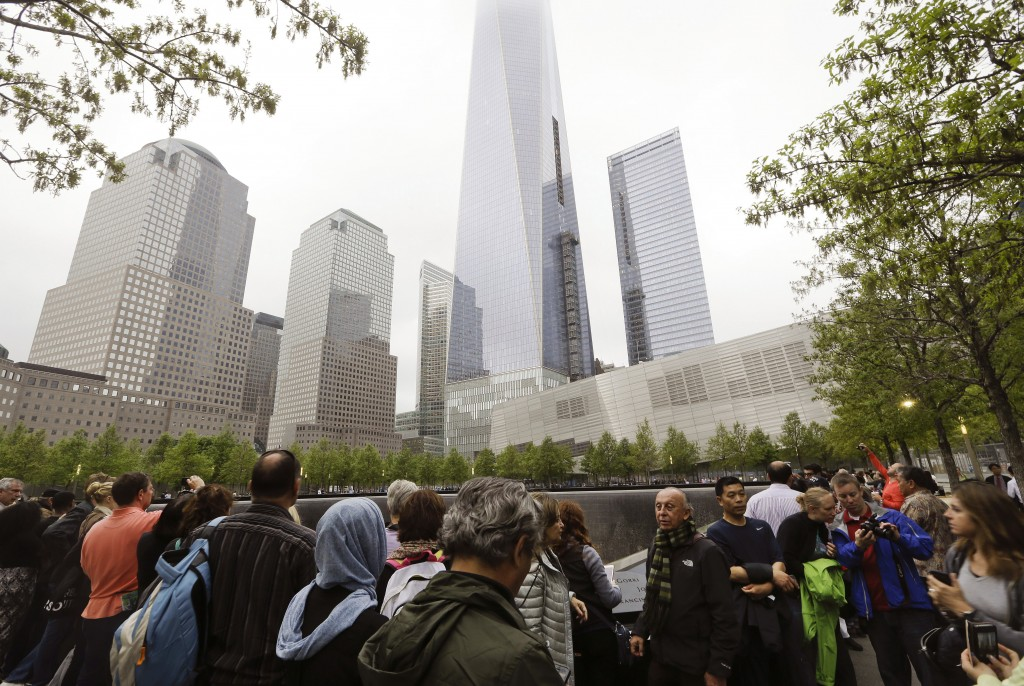 FILE- In this May 15, 2015 file photo, visitors gather near the pools at the 9/11 Memorial in New York. As they have done 17 times before, a crowd of