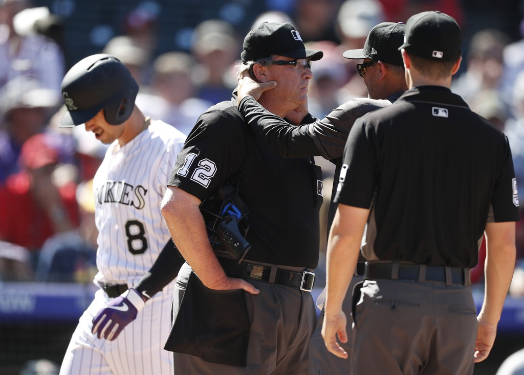 Home plate umpire Gerry Davis (12) is checked by Colorado Rockies trainer Keith Dugger after Davis was hit in the head by a foul ball off the bat of J...