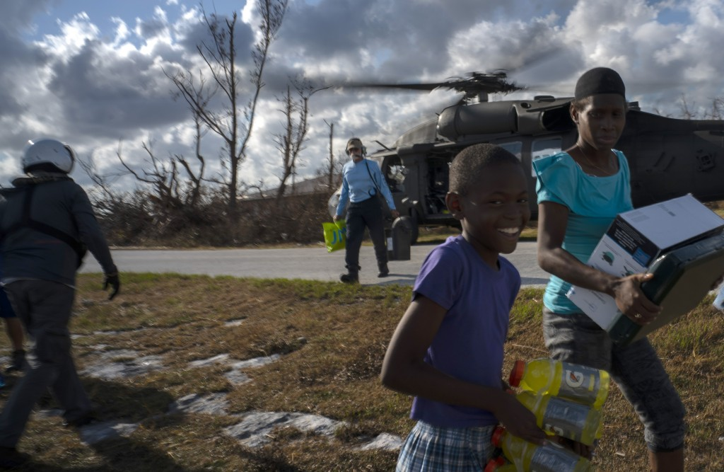 Ayfon Minus, 8, collects donated food that was brought by helicopter from Freeport to the Hurricane Dorian destroyed village of High Rock, Grand Baham...