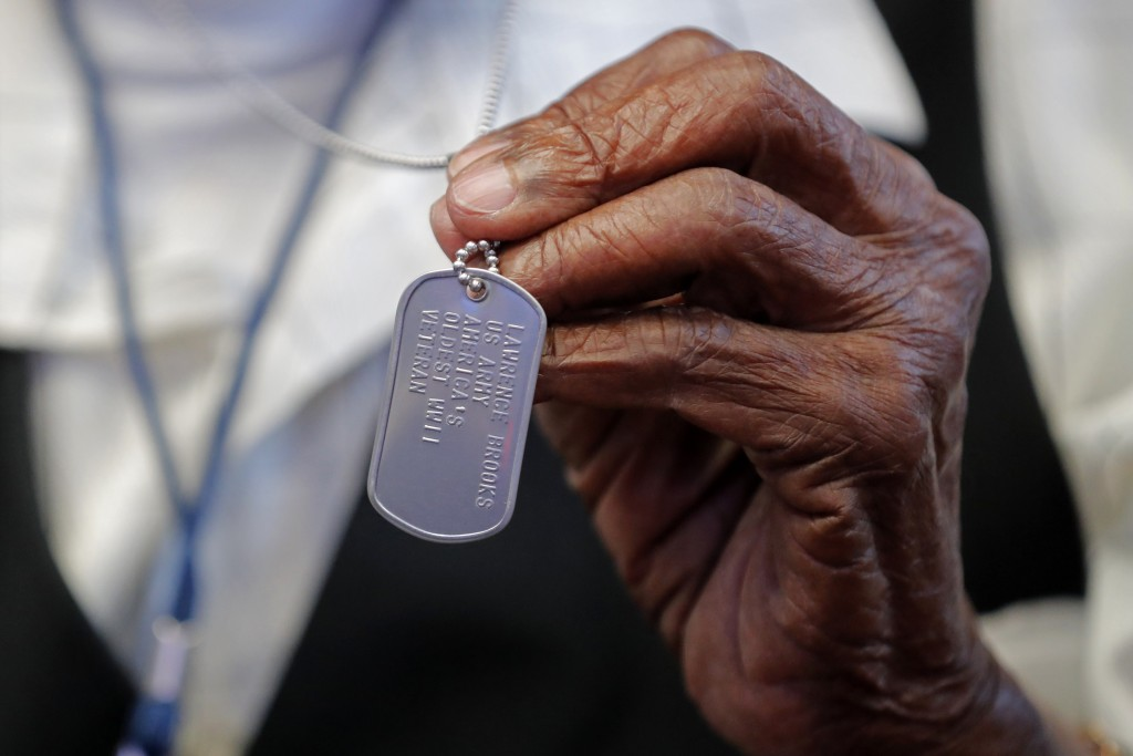 World War II veteran Lawrence Brooks holds a dog tag honoring him as the oldest living World War II veteran, as he celebrates his 110th birthday at th