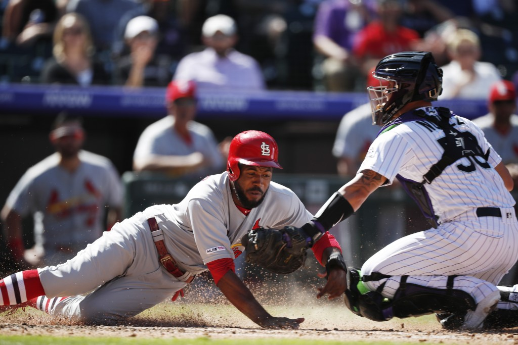 Colorado Rockies catcher Dom Nunez, right, tags out St. Louis Cardinals' Dexter Fowler as he tries to score on a ground ball hit by Paul DeJong in the
