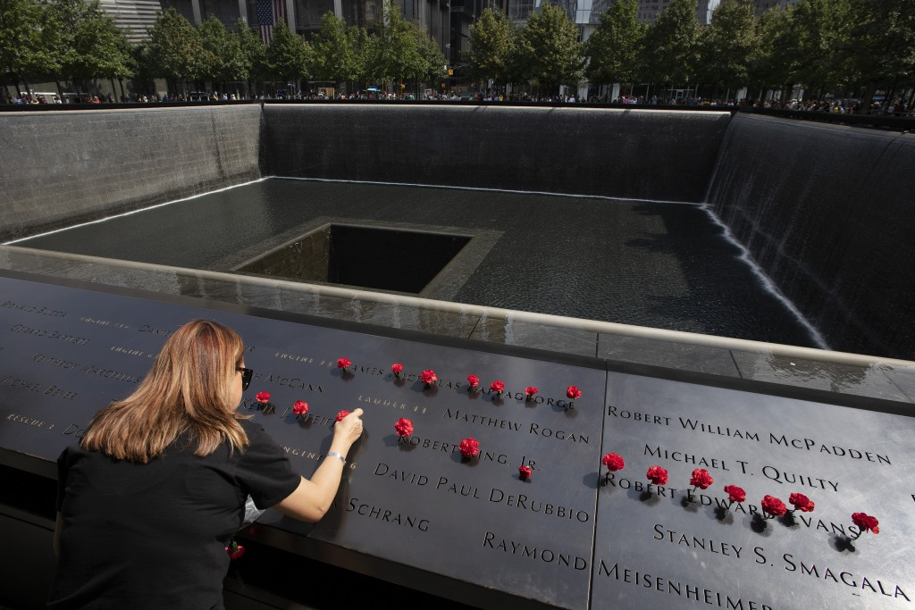 Norma Molina, of San Antonio, Texas, leaves flowers by the names of firefighters from Engine 33 at the September 11 Memorial, Monday, Sept. 9, 2019, i...